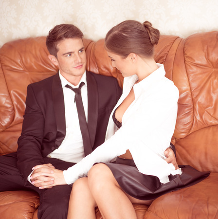 men sex: Very Attractive Couple in Black and White Talking White Sitting on Couch Stock Photo