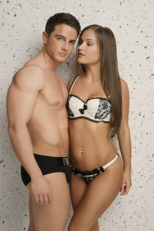 Very Sexy Young Couple in Black and White Underwear Portrait. Isolated on Batik White Wall
