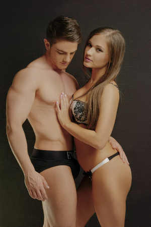 ladies underwear: Young Sexy Couple Very Hot Portrait. Super Hunk Man Wearing Sexy Brief While Partner Wearing Sexy Bra and Panty. Isolated on Gray Background