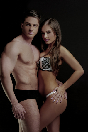 emphasizing: Young Sexy Couple Posing for Underwear Fashion, Isolated on Black. Emphasizing Curves and Lines