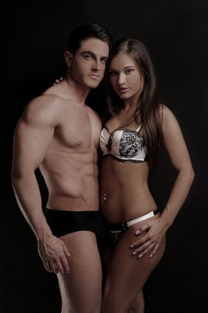 belleza masculina: Muy Pareja caliente que desgasta la manera atractiva de la ropa interior que mira la c�mara. Aislado en Negro.