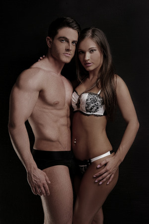 undergarments: Very Hot Couple Wearing Sexy Underwear Fashion Looking at Camera. Isolated on Black.
