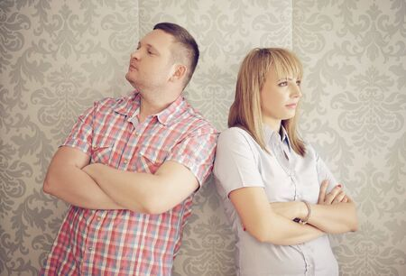 facing away: Couple ignoring each other after an argument standing facing away from one another with serious disgruntled expressions , against retro patterned beige wallpaper Stock Photo