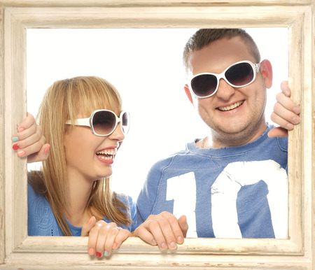 looking through frame: Loving couple in picture frame. Beautiful young couple looking through a picture frame and smiling wearing glasses