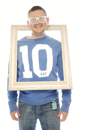 Cute playful man in trendy blinder sunglasses wearing a number 10 shirt smiling cheekily at the camera with his head through a vintage wooden picture frame