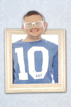 blinder: Cute playful man in trendy blinder sunglasses wearing a number 10 shirt smiling cheekily at the camera with his head through a vintage wooden picture frame