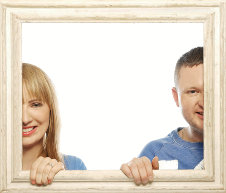 looking through frame: Loving couple in picture frame. Beautiful young couple looking through a picture frame and smiling