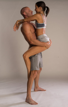 Athletic physical romantic couple with the attractive young woman balancing on the thigh of her muscular sexy boyfriend who is shirtless and barefoot