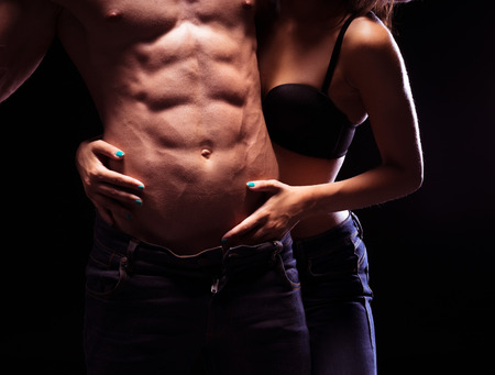 非常にセクシーな男性 6 パック Abs. 黒い背景に分離を渇望する女性