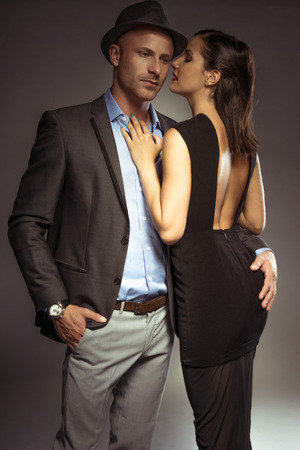 'evening wear': Attractive sexy couple in trendy evening wear on a romantic night out standing in an intimate embrace with the suave young man looking down at the floor as the woman turns to look over her shoulder Stock Photo