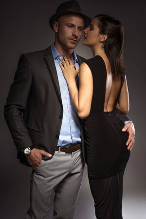 suave: Attractive sexy couple in trendy evening wear on a romantic night out standing in an intimate embrace with the suave young man looking down at the floor as the woman turns to look over her shoulder Stock Photo