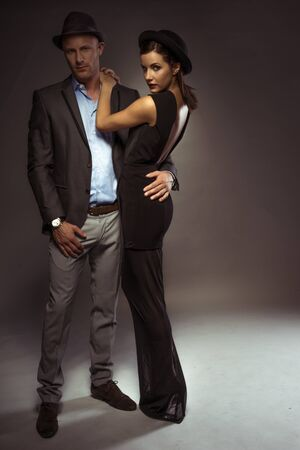 sexy couple embrace: Attractive sexy couple in trendy evening wear on a romantic night out standing in an intimate embrace with the suave young man looking down at the floor as the woman turns to look over her shoulder Stock Photo