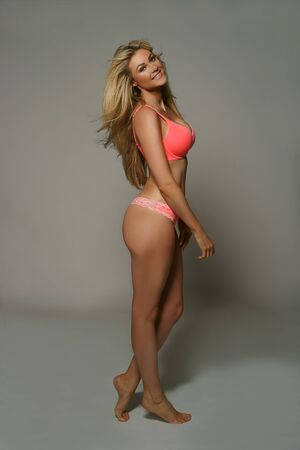 shapely legs: Gorgeous sexy busty blond woman in a bikini posing sideways showing off her shapely legs, and bottom and turning to look at the camera with a beautiful smile, on grey