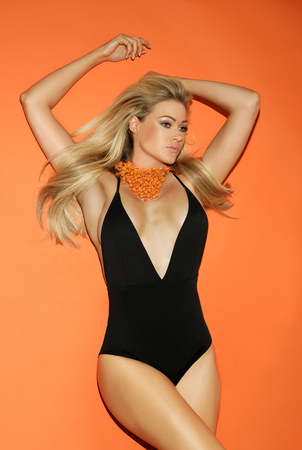 blonde bikini: Beautiful curvaceous blond woman in a swimsuit with her long hair blowing in the breeze and arms raised in the air wearing an orange scarf on a matching orange background