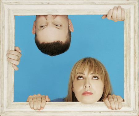 White Couple Behind Wooden Frame While Man in Upside Down Position, Isolated on Sky Blue Background. photo