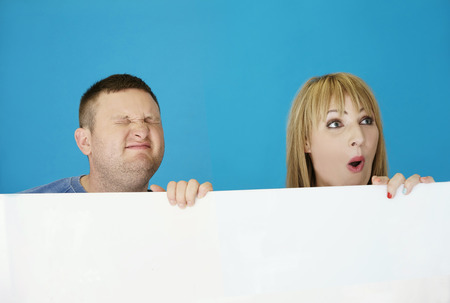 middle age couple: Middle Age Couple Playing Behind White Platform, Isolated on Sky Blue Background. Stock Photo