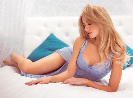 sensual blonde woman wearing blue lingerie sitting on the chair in her bedroom Stock Photo