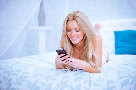decibel: Cheerful blond girl listening to music on her smartphone on the bed