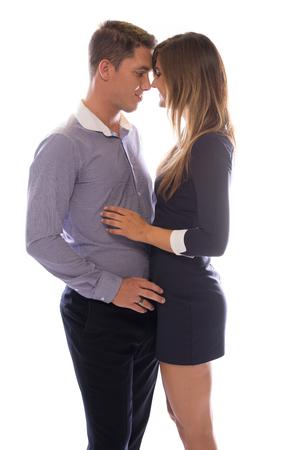 parejas enamoradas: Joven pareja cariñosa tocar frentes, ya que comparten un momento blando de pie muy juntos cara a cara, en blanco