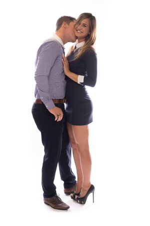 lustful: Romantic young man necking with his girlfriend kissing her on the throat as she smiles happily at the camera, full length in profile on white Stock Photo