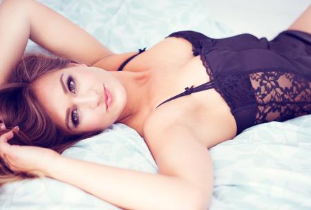 mujer sola: Mujer bonita joven en la cama con un vestido sexy lencería