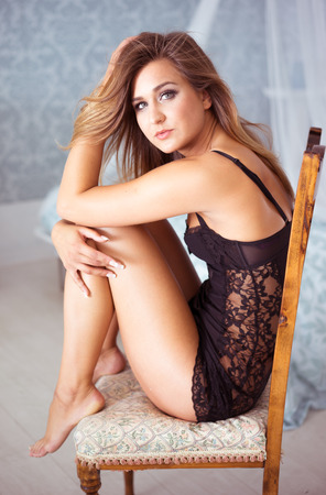 negligee: Leggy young woman wearing a sexy lingerie dress sitting on a chair waiting