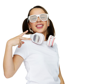 head tilted: Trendy attractive young girl in white shutter shades standing proudly with her head tilted back and a set of headphones for her music around her neck, isolated on white Stock Photo
