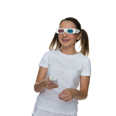 stereoscopic: Young girl with her hair in pigtails wearing 3d stereoscopic glasses and holding a remote control for a video or film, ioslated on white Stock Photo