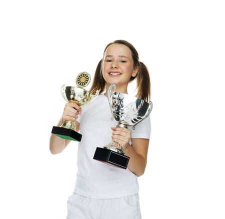 12 13: Proud young girl holding two trophies that she has won in class at school or in a sports competition, isolated on white