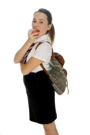 young schoolgirl: Young schoolgirl standing eating a healthy red apple with her backpack on her back standing sideways looking at the camera, on white Stock Photo