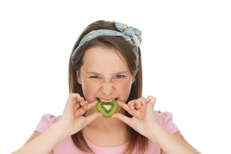 12 13: Young girl biting into a slice of kiwifruit with a disdainful look on her face as though she finds the taste unpleasant, on white