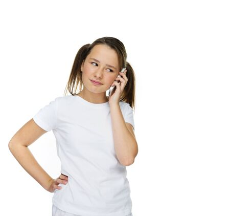 dubious: Young girl with a puzzled expression chatting on her mobile pone looking dubious about what is being said, isolated on white