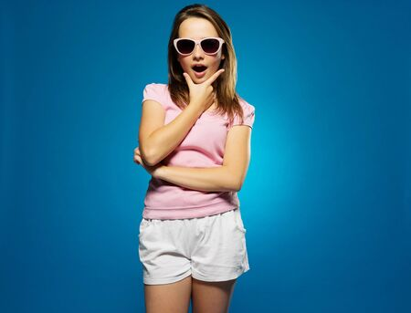 seductive expression: Fashionable young girl in trendy sunglasses and summer shorts with a look of surprise and amazement looking at the camera with her mouth open, on blue