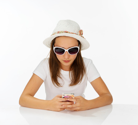 edu: Fashionable yong girl in a trendy hat and sunglasses sitting at a table sending an sms on her mobile phone