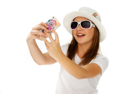 preety: Beautiful chic young girl in a trendy white hat and sunglasses posing for a selfie on her mobile phone isolated on white