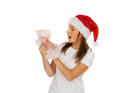 pink teddy bear: Young girl in red Santa Hat looking at a small plush pink teddy bear Christmas gift that she is holding in her hands with her mouth open in surprise, isolated on white
