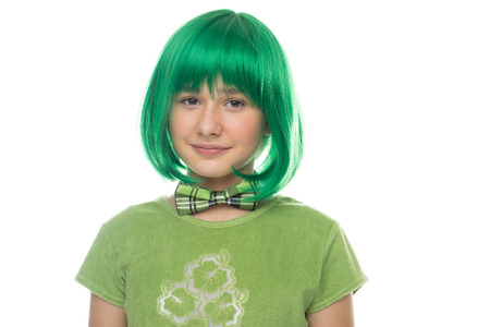 12 13: Cute pretty young girl wearing a bright green wig and matching bow tie looking at the camera with a whimsical expression, isolated on white