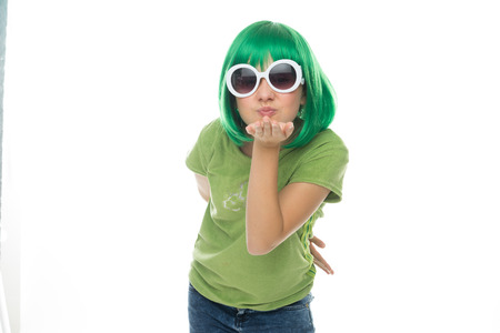 12 13: Romantic young girl in a green wig and sunglasses blowing her sweetheart a kiss across her palm, isolated on white
