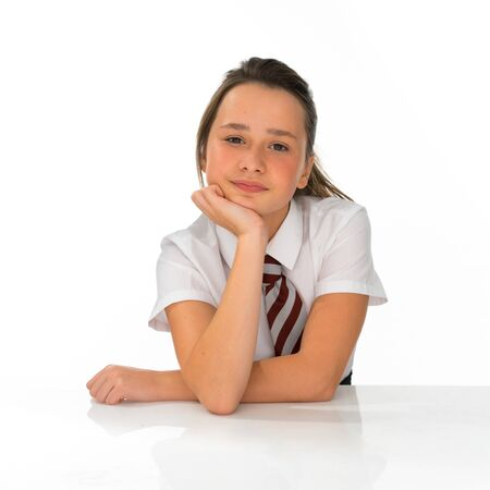 13: Bored young girl in school uniform sitting at a table with her chin resting on her hand smiling at the camera, on white