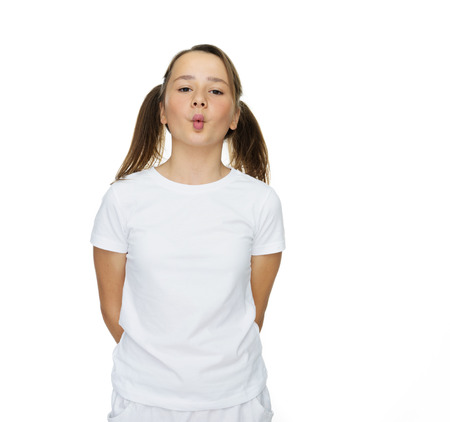 puckering lips: Cute young girl puckering up for a kiss standing with her hands behind her back leaning forwards with pouting lips, isolated on white Stock Photo