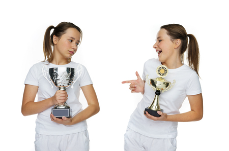 Two Young Pretty Girls in White Holding Trophies Pose. Isolated on Pure White Background.