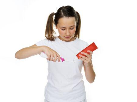 red tube: Chica joven que pone pasta de dientes en un cepillo de dientes el�ctrico de un tubo rojo, aislado en blanco