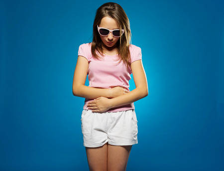 stomache: Young girl with a stomach ache clutching her belly with her hands looking down dejectedly at the floor, on blue Stock Photo