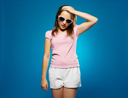 forehand: Trendy young girl in summer shorts and sunglasses with a headache clutching her forehand with her hand and grimacing in pain, on blue