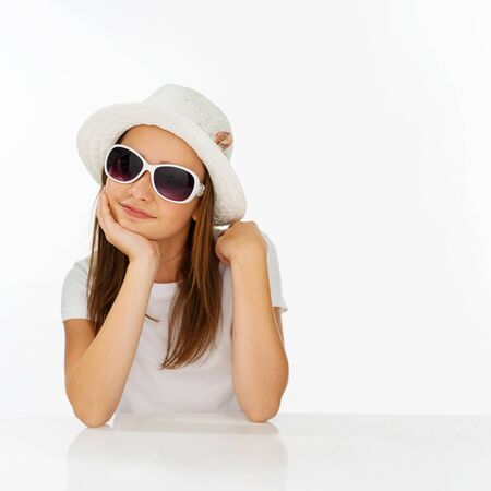 preety: Thoughtful pretty young girl in a fashionable outfit wearing a trendy white hat and sunglasses sitting resting her chin on her hand looking at the camera
