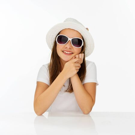 preety: Cute trendy young girl in a white sunhat and matching sunglasses giving the camera a beautiful smile Stock Photo