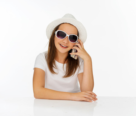 edu: Trendy young girl in a white sunhat and sunglasses chatting on her mobile phone and looking at the camera with a smile