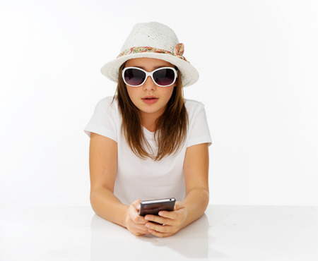 edu: Beautiful little girl in a fashionable hat and sunglasses sitting reading a text message on her mobile phone, on white Stock Photo