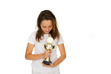 edu: Young girl clasping a sporting trophy closely to her chest as she looks down with a proud delighted expression at her win, on white Stock Photo