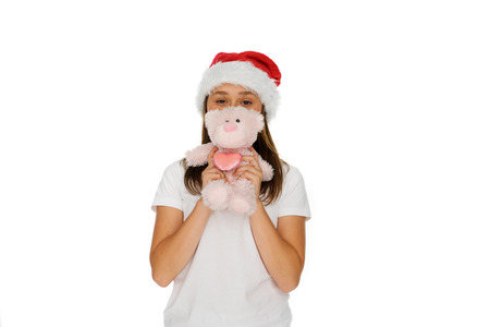 pink teddy bear: Young girl in a festive red Santa hat with a fluffy pink teddy bear held up in front of her face, isolated on white Stock Photo